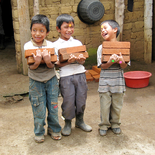 """As we were building a stove for a family, the little boys wanted so badly to help. We told them they could carry bricks for us. They continually tried to outdo one another and would giggle every time they would stack the bricks in their arms. You can see the stickers we gave them on their hands and forehead. I love this picture because it so depicts the love and work ethic that we witnessed in the Guatemalan people."""