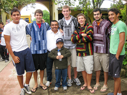 """For me much of St Thomas More's Guatemalan mission is about sharing our cultures. In this photo, the tall boys on the end are Guatemalan and they're wearing American t-shirts. Tony and his son in the middle are also Guatemalan but proudly wearing their American clothing. The four other boys/men are happy to be wearing their Guatemalan pullovers."""